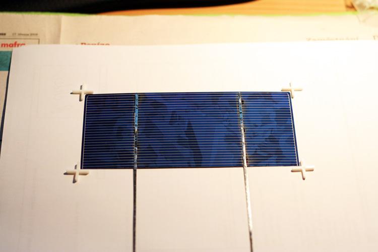 Fotovoltaický článek (poloviční) s vodivými páskami na sběrnicích